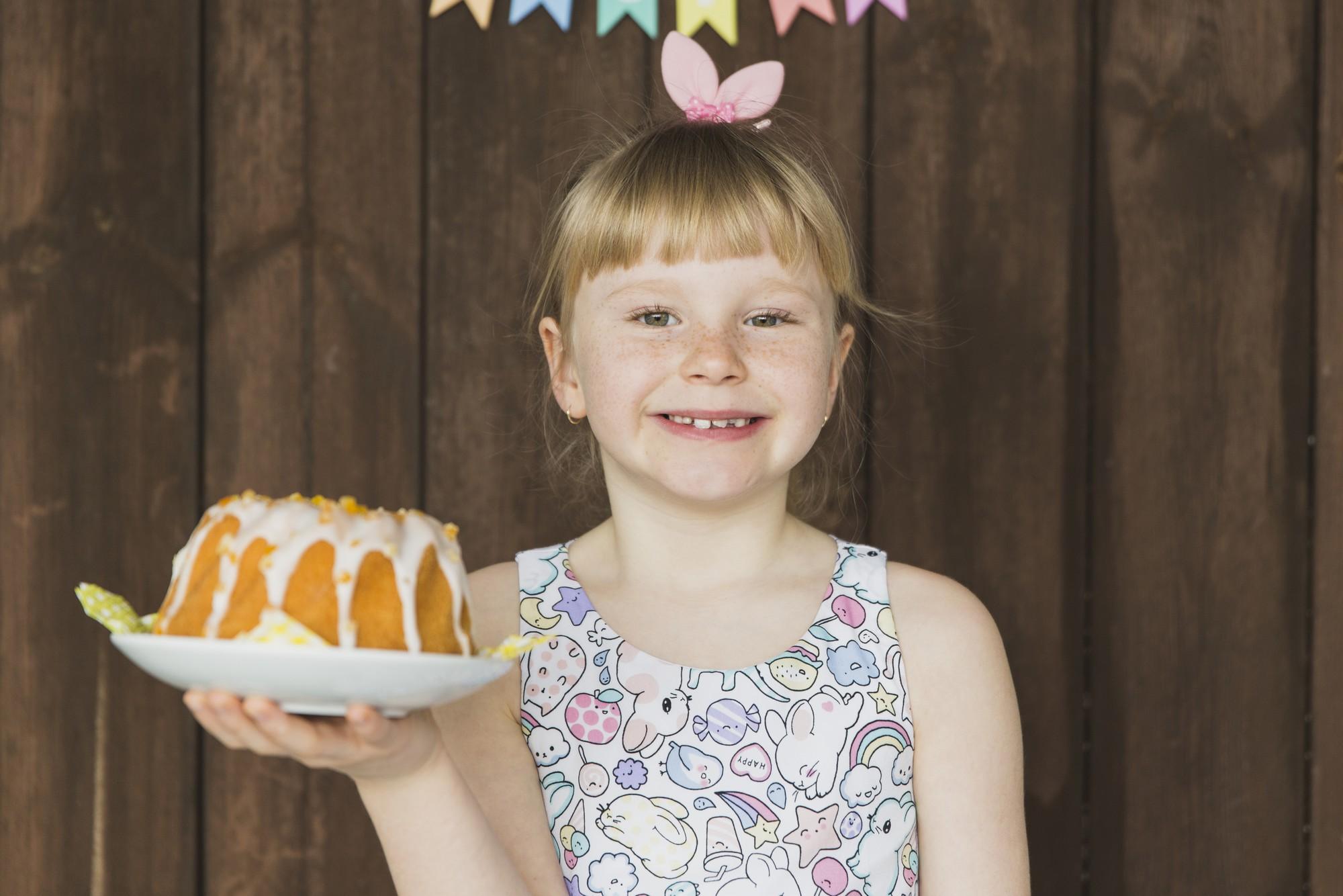 Criança segurando bolo feito com a mãe